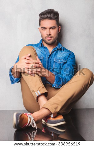 stylish man sitting in studio background legs crossed holding his knee while looking at the camera - stock photo