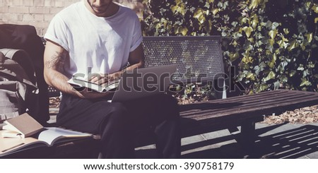 Stylish man wearing white tshirt sitting city park and reading book. Studying at the University, working new project,  preparation for exams. Books, laptop, backpack bench. Wide mockup