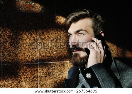 stylish man with a beard talking on cell phone