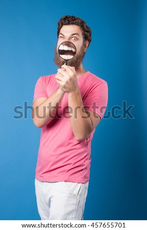 Stylish man with a magnifying glass, mouth closeup.A man with a magnifying glass on a blue background.MAGNIFYING GLASS ON HER FACE,MOUTH AND TEETH.Portrait of a Man. beautiful freak.mAN hipster - stock photo