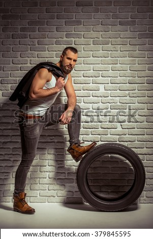 Stylish man with beard holding a leather jacket, looking at camera and leaning on a tire, standing against brick wall - stock photo