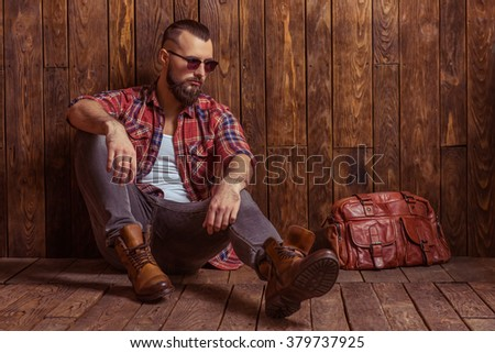 Stylish man with beard in casual shirt and sunglasses looking away, sitting on a wooden background - stock photo