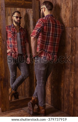Stylish man with beard in casual shirt and sunglasses looking in the mirror, standing in a wooden room - stock photo