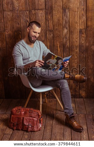 Stylish man with beard in gray sweater reading a magazine and smiling, sitting on a chair against wooden background - stock photo