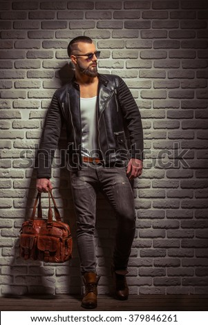 Stylish man with beard in leather jacket and sunglasses holding a brown leather bag, standing against brick wall - stock photo