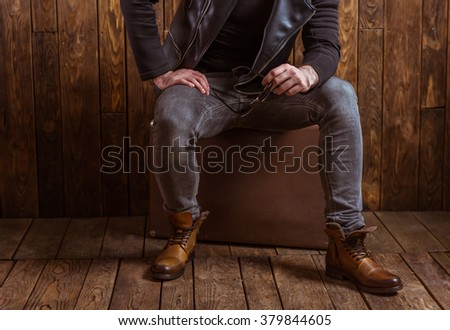 Stylish man with beard in leather jacket holding sunglasses and looking at camera, sitting on a wooden background, cropped - stock photo