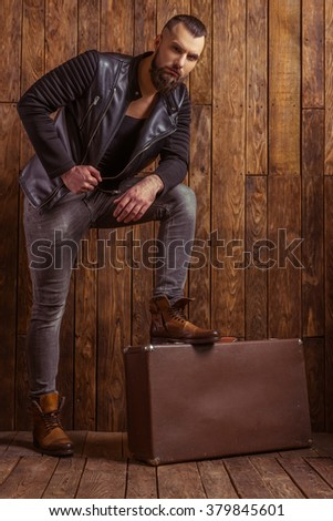 Stylish man with beard in leather jacket leaning on a suitcase and looking at camera, standing on a wooden background - stock photo