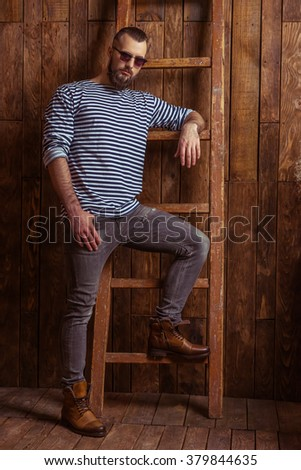 Stylish man with beard in striped vest and sunglasses leaning on a ladder, looking at camera, standing on a wooden background - stock photo