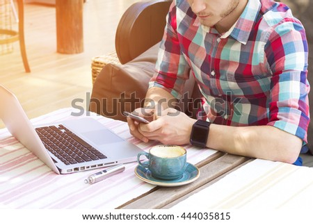 Stylish man with laptop, coffee and e-cigarette typing something on phone. - stock photo
