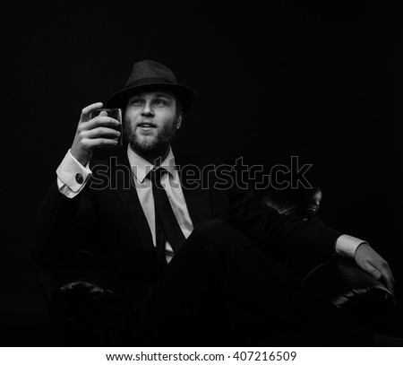 Stylish man with the hat and  glass of whiskey and beard in the chair black and white portrait