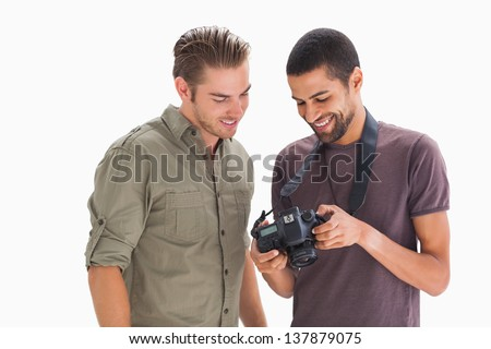 Stylish men looking at digital camera on white background