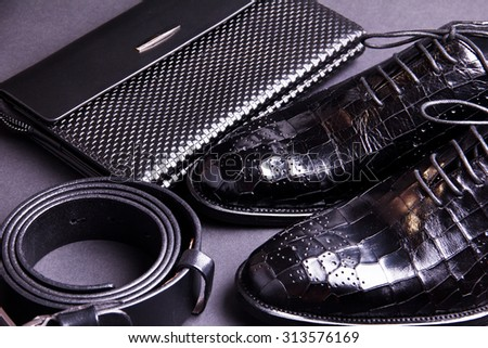 Stylish men's shoes, purse, cellphone and black belt on gray background. Crocodile leather.
