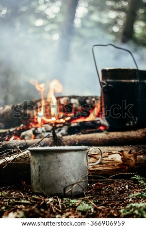 stylish metal cup and kettle in sunny forest in the mountains - stock photo