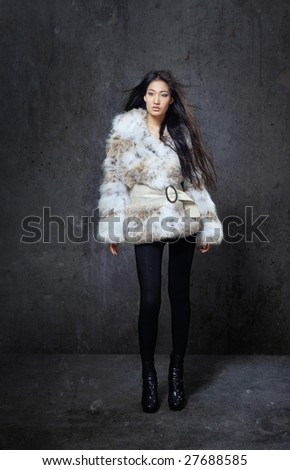 Stylish model in fur coat with blowing hairs in trashy interior - stock photo