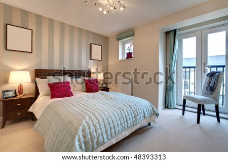 Stylish modern adult bedroom including bed dressed with brightly colored cushions - stock photo