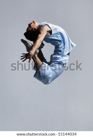 stylish modern ballet dancer jumping on grey - stock photo