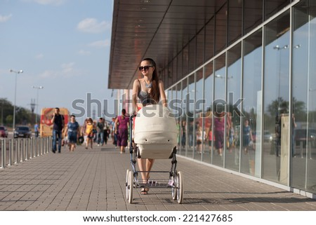 Stylish mom with retro stroller - stock photo