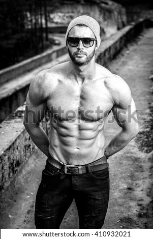 Stylish muscle man posing topless outdoor in urban fashion manner - stock photo