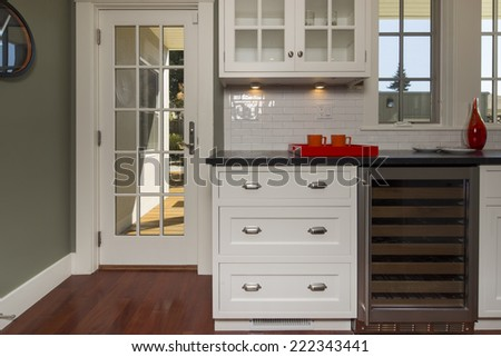 Stylish new kitchen in white with black granite counter tops with stainless steel oven, stove, dual zone wine cooler. Traditional french door leads to outdoors.  - stock photo