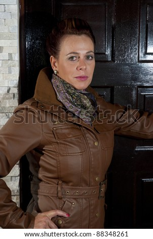Stylish older caucasian woman in a brown leather jacket, posing casually indoors - stock photo