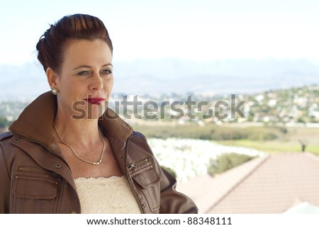 Stylish older caucasian woman in a brown leather jacket, posing casually outdoors, overlooking some houses - stock photo
