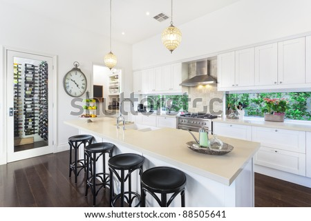 Stylish open plan kitchen with stainless steel appliances - stock photo