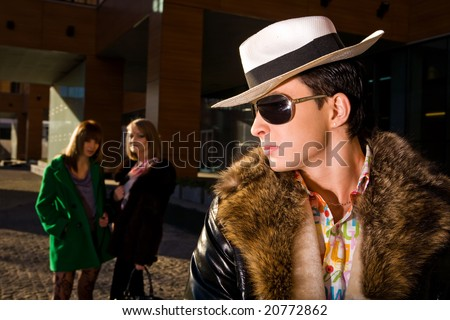 Stylish pimp in a hat and two young women on background outdoors - stock photo