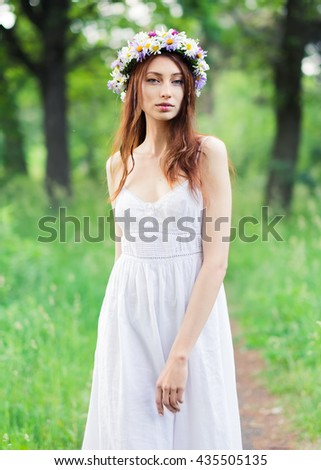 stylish portrait of a beautiful young woman in a long dress in the park in the evening at sunset - stock photo