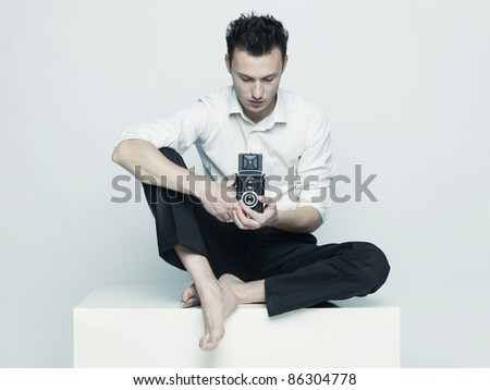 Stylish portrait of a young man with a camera - stock photo
