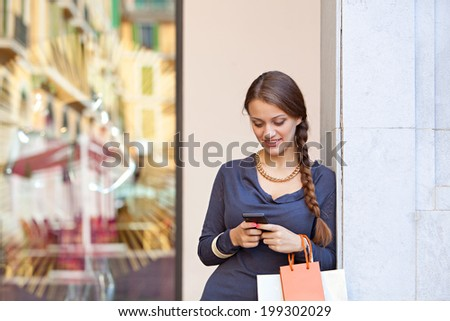 Stylish portrait of an elegant young woman carrying shopping bags and leaning on a column using her smartphone cell while visiting a luxurious shopping mall, lifestyle. Consumerism and technology. - stock photo