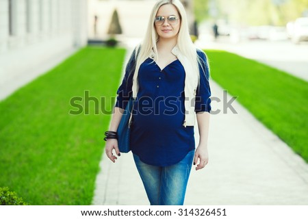 Stylish Pregnancy Concept. Portrait of fashionable mommy with long blond hair wearing casual trendy clothes and going shopping with blue leather bag. Sunny weather. Urban street style. Outdoor shot