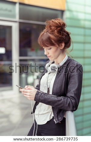 Stylish Pretty Young Woman Typing on her Mobile Phone While Leaning Against the Railings Seriously. - stock photo