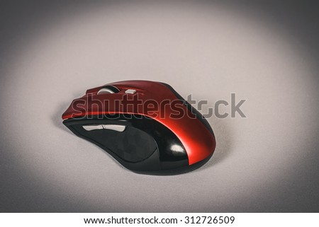 Stylish red and black wireless mouse on a gray background