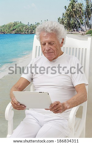 stylish  retirement senior man  seated in summer with, tropical beach background using tablet computer   - stock photo