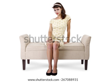 Stylish retro female sitting on a chaise lounge or sofa on white background sitting and waiting - stock photo