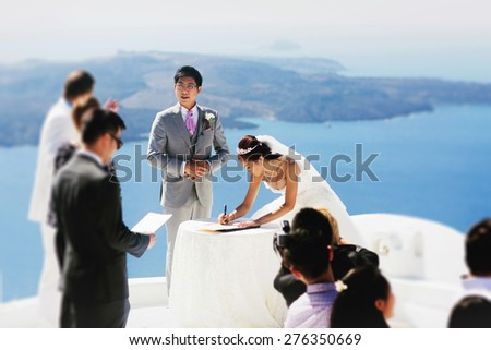 stylish rich asian bride and groom  put sign wedding tradition on the island of Santorini, Greece sunshine