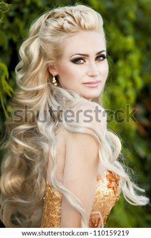 Stylish rich slim girl in sexy golden dress with healthy glossy curly hair in the park. Fashion glamorous shot at vacation resort summer. alluring blond woman in evening dress on nature.Series - stock photo
