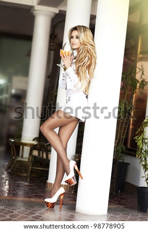 Stylish rich slim girl resting with orange drink in sexy dress with healthy glossy hair in luxurious interior at hotel villa apartment. Fashion glamorous shot at vacation resort spring-summer - stock photo