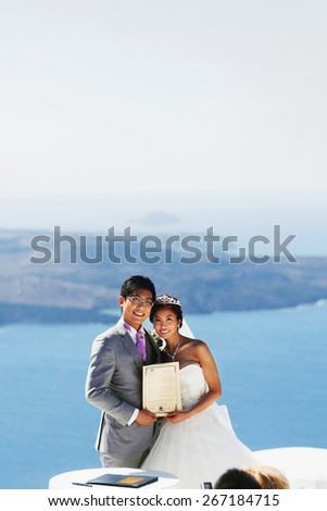 stylish rich smiling asian bride and groom  wedding posing with certificate in island Santorini greece sunshine