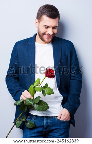 Stylish romantic. Handsome young man holding a flower while standing against grey background - stock photo