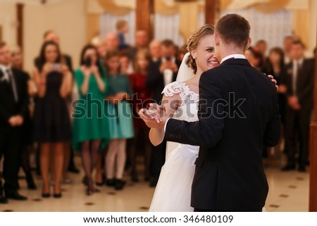 Stylish romantic young couple dancing waltz on their wedding day in luxury restaurant hall against the backdrop of crowds. Beautiful blonde bride in white dress.  - stock photo