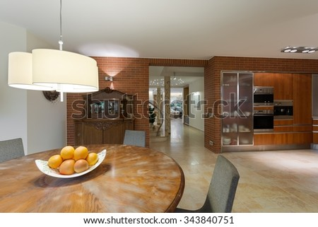 Stylish round wooden table in contemporary kitchen  - stock photo