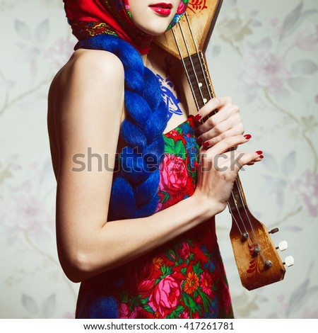 Stylish Russian Girl Concept. Portrait of beautiful young woman with great plait, perfect make-up posing over flower background in Russian national dress. Retro, kitsch, pop-art style. Studio shot - stock photo
