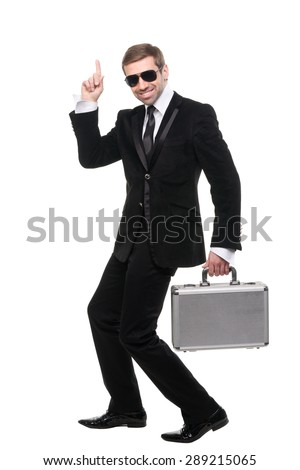 Stylish security guard with a metal suitcase. Full length. Isolated over white background