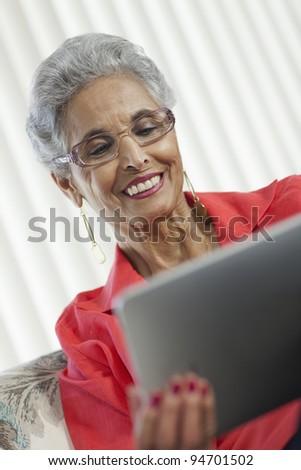 Stylish senior Black woman using a digital tablet - stock photo