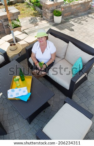 Stylish senior woman sitting on a wicker bench with upholstered cushions drinking iced water with lemon and mint on a paved brick outdoor patio in a lifestyle concept, high angle view - stock photo