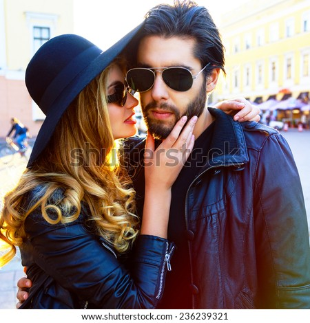 Stylish sexy couple in love hugs at the city street at evening sunlight. Wearing black rock glamor outfit and sunglasses. - stock photo