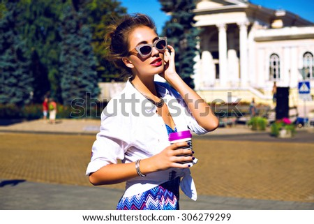 Stylish sexy girl traveling at Europe, drinking tasty latte, enjoy her trip, wearing bright printed summer romper, trendy jewelry and vintage sparkled sunglasses, bright toned colors. - stock photo