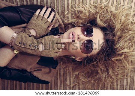 Stylish sexy hot glamour young woman with glasses gloves lying on the couch crossed arms portrait - stock photo