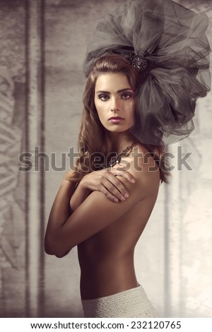 stylish sexy naked woman posing with big tulle fashion accessory in the hair and cute necklace, covering her breast and looking in camera  - stock photo